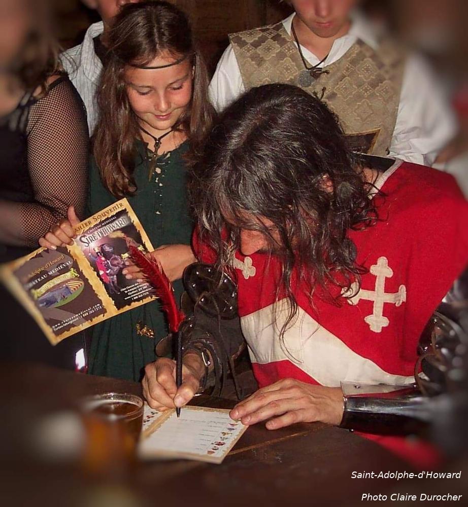 un homme habillé en chevalier signe des autographes
