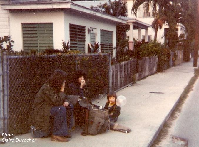 deux femmes et un enfant mangent sur le trottoir assis sur leur sac à dos