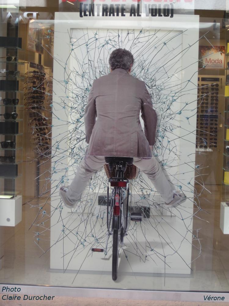 un homme fracasse une vitre avec son vélo