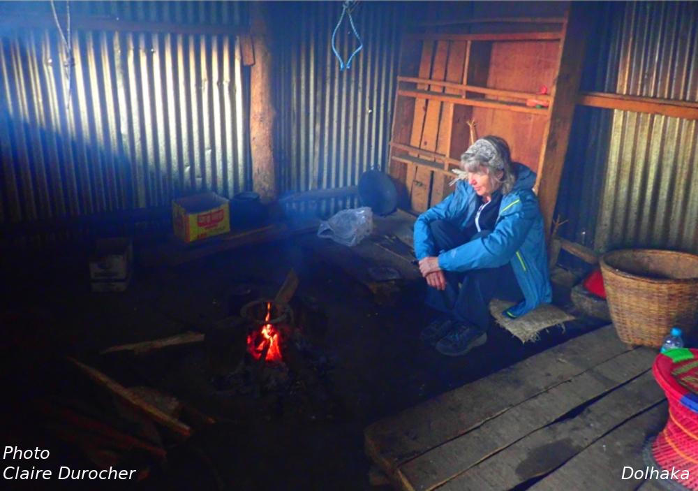 une femme assise devant un feu de bois