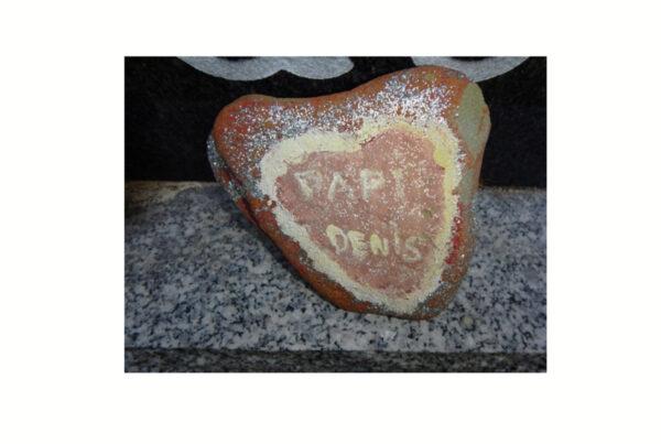 pierre enforme de coeur déposée devant une pierre tombale