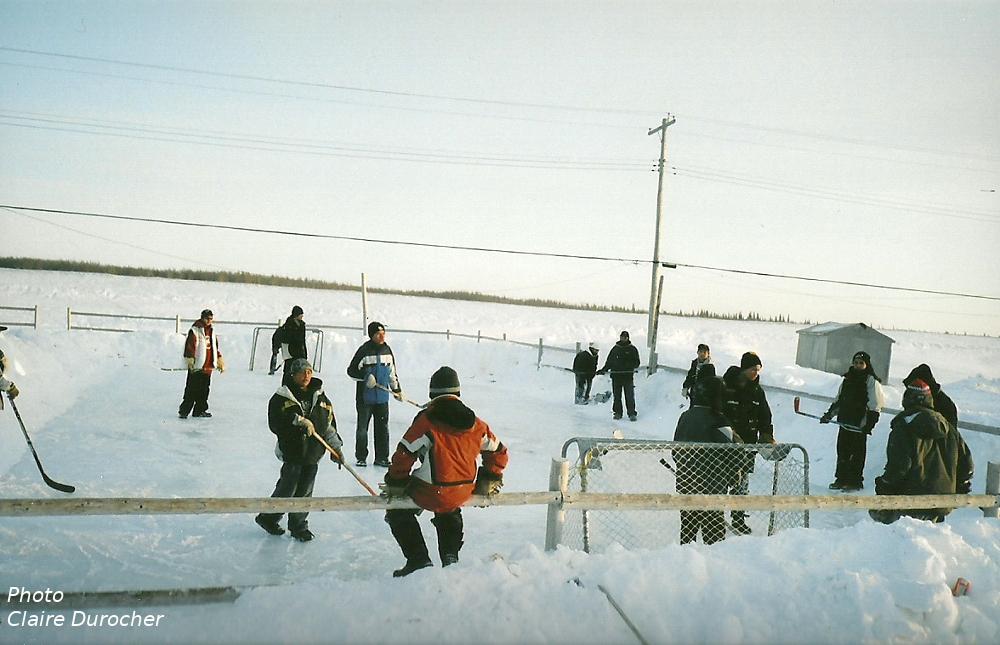 jeunes jouent au hockey sur une patinoire extérieure